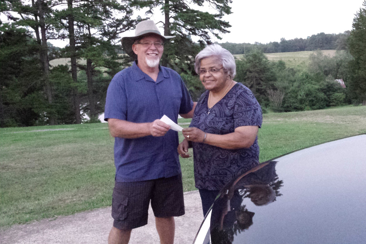 woman handing man a check